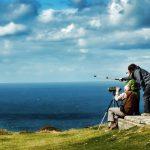 Personas en un acantilado observando con binoculares el horizonte.