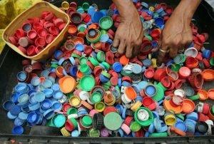 Persona separando tapones de botellas.