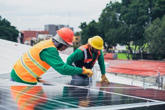 Personas colocando una placa solar.